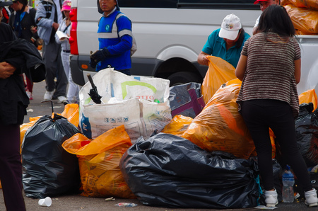 pope: QUITO, ECUADOR - JULY 7, 2015: After pope Francisco mass, garbage cleaners putting all the trash in bags. Editorial