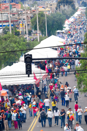 multiple ethnicity: QUITO, ECUADOR - JULY 7, 2015: Several focus on red loght and cables, behind street full of people walking to arrive to pope Francisco mass.