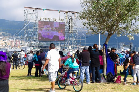 big screen: QUITO, ECUADOR - JULY 7, 2015: People looking in a big screen the little road that pope Francisco made around the mass in Ecuador.
