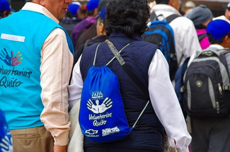 identified: QUITO, ECUADOR - JULY 7, 2015: Two voluntarees walking around pope Francisco mass event, vests and backpacks to identified them.