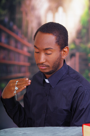 clerical: Catholic priest wearing traditional clerical collar shirt standing performing sign of the cross and holding rosary in hand, religion concept.