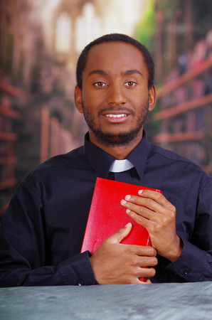 Catholic priest wearing traditional clerical collar shirt sitting and holding bible looking into camera, religion concept. Stock Photo