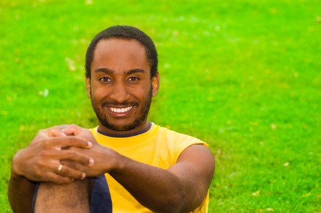 holding in arm: Man wearing yellow shirt and blue shorts sitting on green grass, holding arm around knee smiling to camera, training concept.