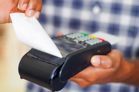 Uomo che porta il pagamento di elaborazione blu camicia bianca modello quadrato con carta di credito terminale davanti alla macchina fotografica, primo piano l'angolo. Archivio Fotografico