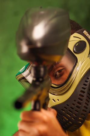 facing to camera: Closeup headshot man wearing green and black protection facial mask facing camera pointing paintball gun.