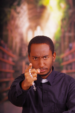 Catholic priest wearing traditional clerical collar shirt standing facing camera, holding hands out with rosary cross, looking forward, religion concept. Stock Photo