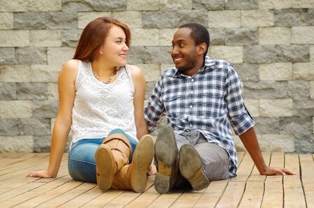 mixed marriage: Interracial charming couple wearing casual clothes sitting on wooden surface posing for camera staring at each other, grey brick wall background.