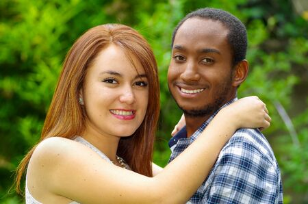 ethnic mix: Interracial charming couple wearing casual clothes embracing and posing for camera in outdoors environment. Stock Photo