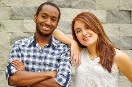 mixed marriage: Interracial charming couple wearing casual clothes posing for camera and embracing in front of grey brick wall.