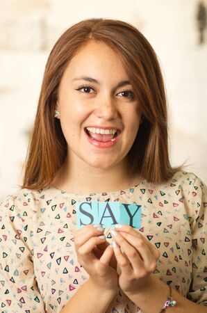 Headshot charming brunette woman holding up small letters spelling the word say and smiling to camera.