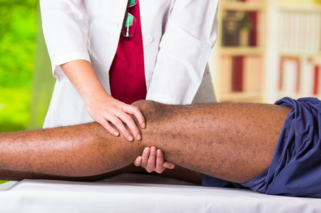 Man getting knee treatment from physio therapist, her hands holding his leg and applying massage, injury medical concept.