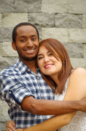 ethnic mix: Interracial charming couple wearing casual clothes posing for camera and embracing in front of grey brick wall.