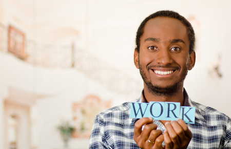 Headshot handsome man holding up small letters spelling the word work and smiling to camera.