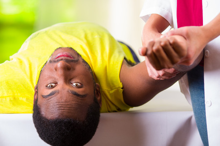 strengthen hand: Man lying down getting physical shoulder treatment from physio therapist, patient looking into camera while her hands working on his upper arm area, medical concept. Stock Photo