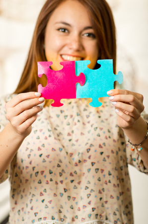 Headshot charming brunette woman holding up big puzzle pieces in pink and blue, smiling happily to camera, white studio background.