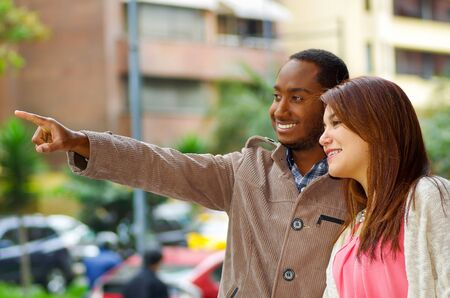 mixed marriage: Interracial happy charming couple wearing casual clothes interacting for camera in outdoors urban environment. Stock Photo