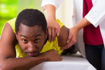 man lying down: Man lying down getting physical shoulder treatment from physio therapist, patient looking into camera while her hands working on his upper arm area, medical concept. Stock Photo
