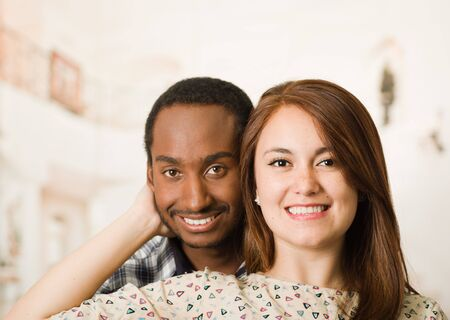 Happy interracial couple headshots posing happily and smiling, woman holding boyfriends head with her hand, white studio background.