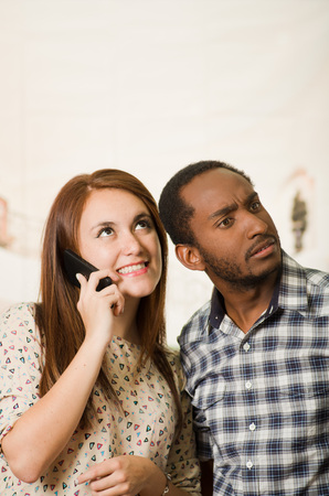 Interracial charming couple wearing casual clothes posing interacting friendly, woman talking on cell phone and man listening in, white studio background. Stock Photo