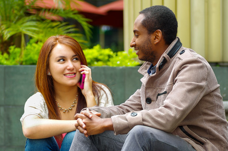ethnic mix: Interracial happy charming couple sitting on steps in front of building interacting and smiling for camera. Stock Photo