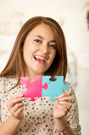 red skinned: Headshot charming brunette woman holding up big puzzle pieces in pink and blue, smiling happily to camera, white studio background.