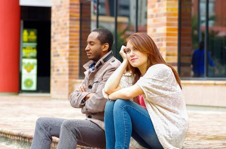 simulating: Interracial upset couple sitting on steps in front of building, simulating argument for camera.