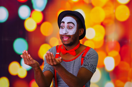 pantomima: Pantomima hombre con pintura facial posando para la cámara de retención soplando el cuerno, luces de fondo borroso.