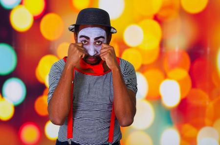 pantomima: hombre pantomima disparos en la cabeza con la pintura de la cara que presenta para la c�mara con las manos interactuar frota los ojos, fondo borroso de las luces.