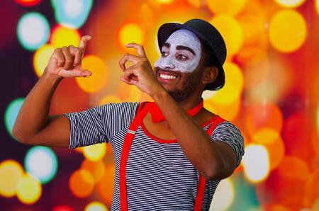 pantomima: Pantomime man wearing facial paint posing for camera, using hands interacting body language, blurry lights background.