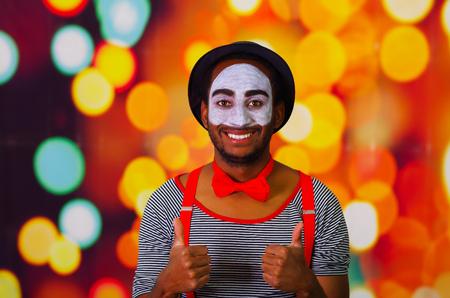 pantomima: Pantomima hombre con pintura facial presenta para la c�mara interactuar dando pulgar hacia arriba sonriente, Fondo de las luces borrosas. Foto de archivo