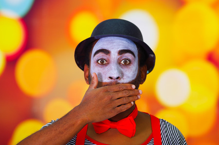 pantomima: Headshot pantomime man with facial paint posing for camera using hands to cover mouth, blurry lights background. Foto de archivo