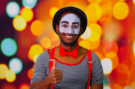 pantomima: Pantomime man with facial paint posing for camera interacting giving thumbs up smiling, blurry lights background.