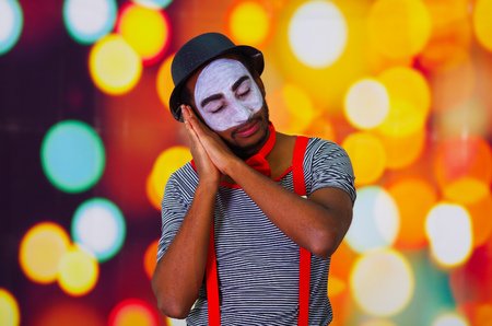 pantomima: Headshot pantomime man with facial paint posing for camera using hands interacting sleeping, blurry lights background.
