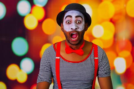 pantomima: Pantomima hombre lleva la pintura facial presenta para la c�mara interactuando hace expresiones divertidas, luces de fondo borroso.