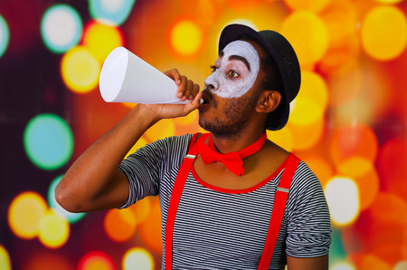 pantomima: Pantomime man with facial paint posing for camera holding blowing horn, blurry lights background.