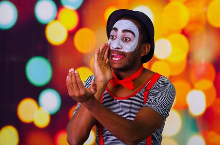 pantomima: Pantomima hombre con pintura facial posando para la c�mara de retenci�n soplando el cuerno, luces de fondo borroso.