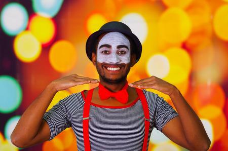 pantomima: hombre pantomima disparos en la cabeza con la pintura de la cara que presenta para la cámara con las manos que interactúan, las luces de fondo borroso.
