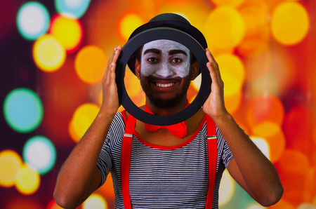 pantomima: Pantomime man with facial paint posing for camera holding circle showing face in middle, blurry lights background.