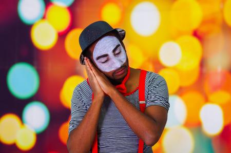 pantomima: hombre pantomima disparos en la cabeza con la pintura de la cara que presenta para la c�mara con las manos que interact�an para dormir, las luces de fondo borroso.