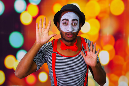 pantomima: Pantomime man with facial paint posing for camera interacting funny using hands, blurry lights background.
