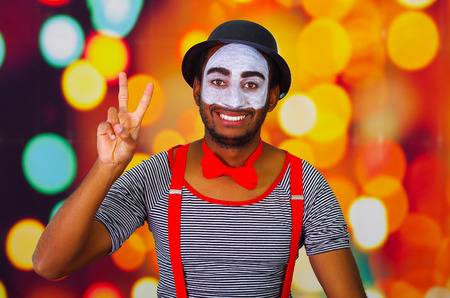 pantomima: Pantomime man wearing facial paint posing for camera, using hands interacting body language, blurry lights background.