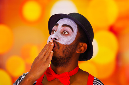 Headshot pantomime man with facial paint posing for camera using hands to cover mouth, blurry lights background. Stock Photo