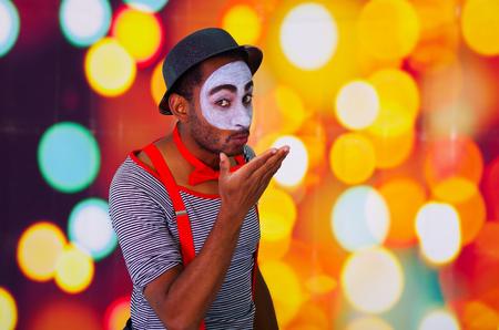pantomima: hombre pantomima disparos en la cabeza con la pintura de la cara que presenta para la c�mara con las manos que interact�an, las luces de fondo borroso.