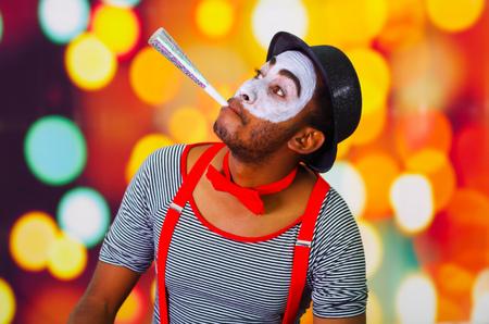 pantomima: hombre pantomima disparos en la cabeza con pintura facial presenta para la c�mara usando el cuerno de soplado, las luces de fondo borroso.
