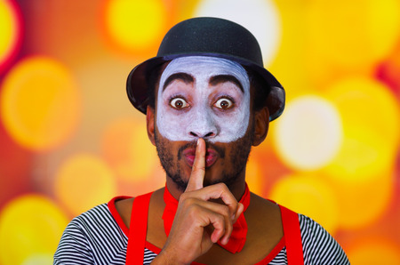 cover mouth: Headshot pantomime man with facial paint posing for camera using hands to cover mouth, blurry lights background. Stock Photo