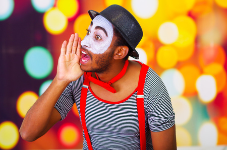 Headshot pantomime man with facial paint posing for camera using hands around mouth yelling, blurry lights background. Stock Photo