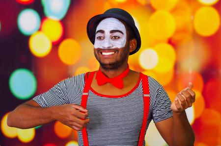 pantomima: Pantomima hombre lleva la pintura facial presenta para la c�mara, el uso de las manos que interact�an lenguaje corporal, las luces de fondo borroso.