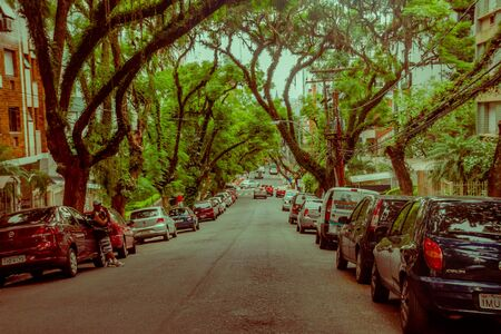 sidewalks: PORTO ALEGRE, BRAZIL - MAY 06, 2016: nice street with big trees in the sidewalks, lot of cars parked outside the buildings.