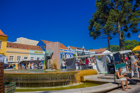 CURITIVA, BRAZIL - MAY 12, 2016: nice fountain located in the middle of the market place, people walking through the market stands.