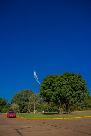 IGUAZU, ARGENTINA - MAY 14, 2016: the national flag of argentina wavig in the middle of the entrance of the national park of iguazu.
